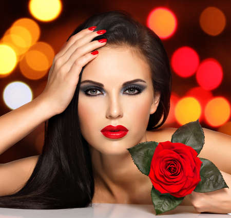 red rose bokeh: Portrait of a beautiful young woman with red lips,  nails and rose flower in hand. Fashion model with black eye makeup posing at studio over night lights balls. Soft bokeh background concept.