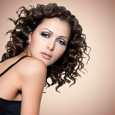 Face of  beautiful adult woman with curly hairs over brown background photo