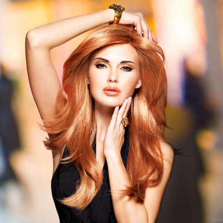 color hair: Beautiful woman with long straight red hair in a black dress touching her face. Fashion model posing at studio