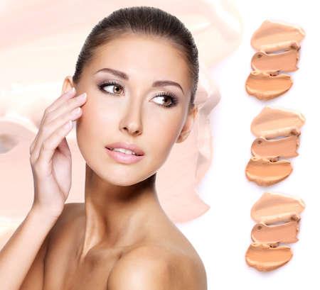 mujer maquillandose: La cara modelo de mujer hermosa con fundamento en la piel de cosméticos de maquillaje.