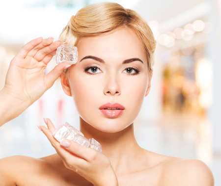 Beautiful young woman applies the ice to face. Skin care concept