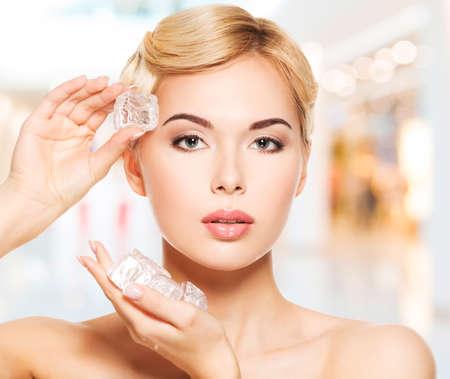 piel rostro: Mujer joven hermosa que aplica el hielo a cara. Concepto de cuidado de la piel