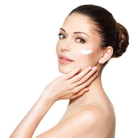 ansikten: Ung kvinna med kosmetisk kräm på en ren nytt ansikte. Hudvård koncept
