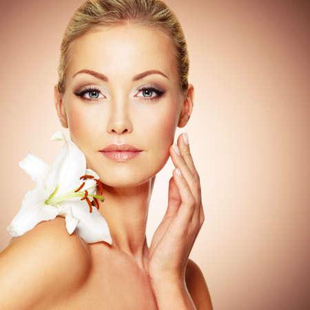 ragazze bionde: Bellezza viso della giovane bella ragazza con il fiore. Femmina pelle toccante.