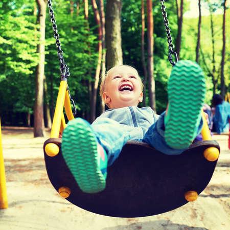 blond boy: Happy little blond boy having fun on a swing in a summer park.