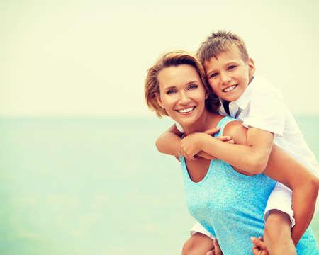 Glückliche lächelnde Mutter und Sohn Spaß am Strand.
