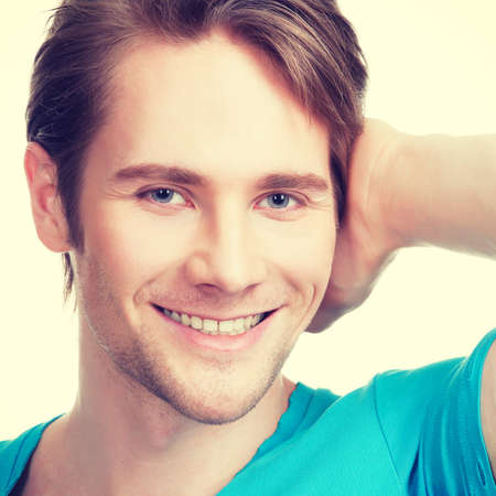 happy young man: Close-up portrait of young happy man in a blue shirt with hand near face -  isolated on white. LANG_EVOIMAGES