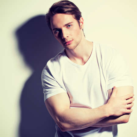 contrast: Portrait of handsome young man in white t-shirt poses over wall with contrast shadows.