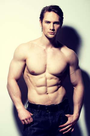 hombre fuerte: Hombre guapo con cuerpo sexy hermosa muscular que presenta en el estudio. LANG_EVOIMAGES