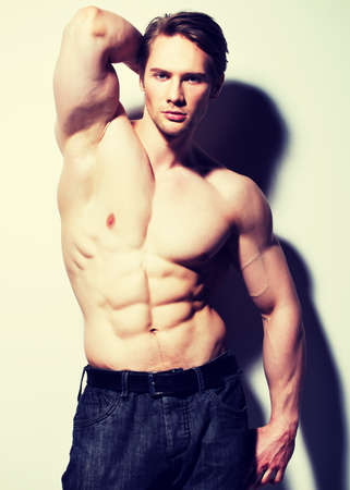shirtless male: Handsome man with sexy muscular beautiful body posing at studio.