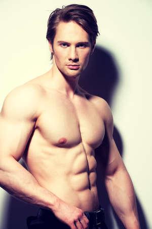 hombres sin camisa: Retrato de un joven musculoso sexy posando sobre un fondo blanco con las sombras de contraste.