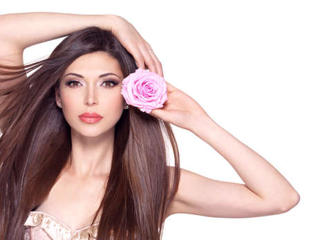 pink posing: Portrait of a beautiful white pretty woman with long straight hair and pink rose at face. Stock Photo