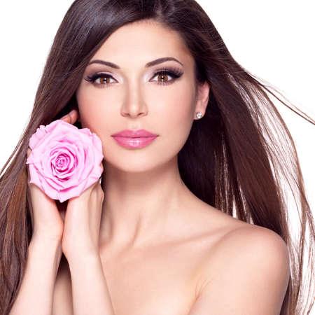 Porträt einer schönen weißen hübsche Frau mit langen glatten Haaren und rosa Rose im Gesicht.