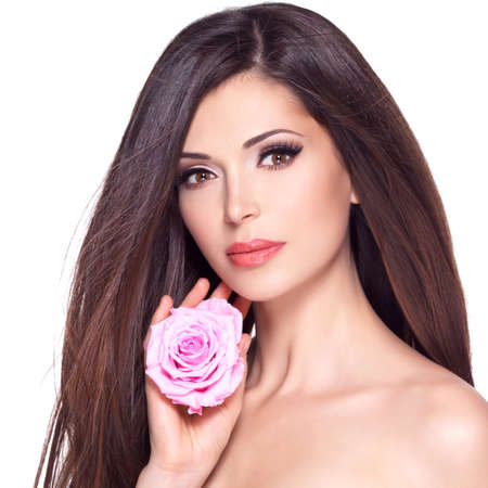Portrait of a beautiful white pretty woman with long straight hair and pink rose at face. Stock Photo