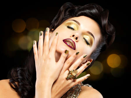 minx: Beautiful brunet woman with golden nails over style background