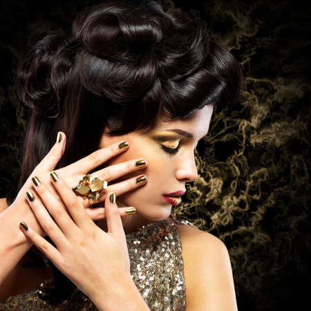 minx: Beautiful  woman with golden nails and fashion hairstyle over creative background Stock Photo