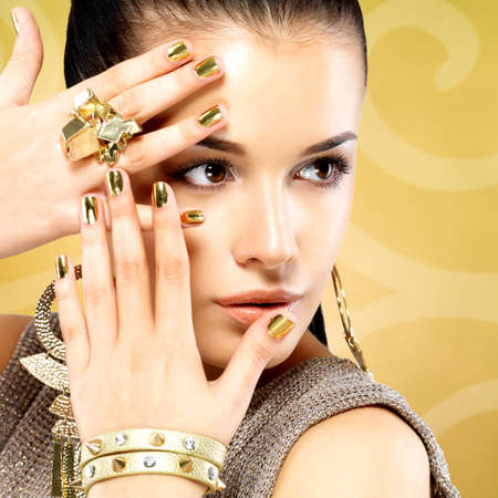 Pretty woman with golden nails and beautiful gold ring over creative background
