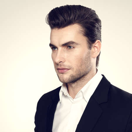 enticement: Closeup face of a fashion young businessman in black suit casual  poses at studio