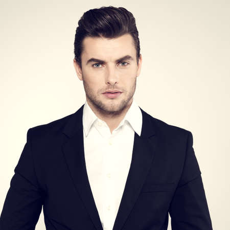 Fashion young businessman black suit casual  poses at studio photo