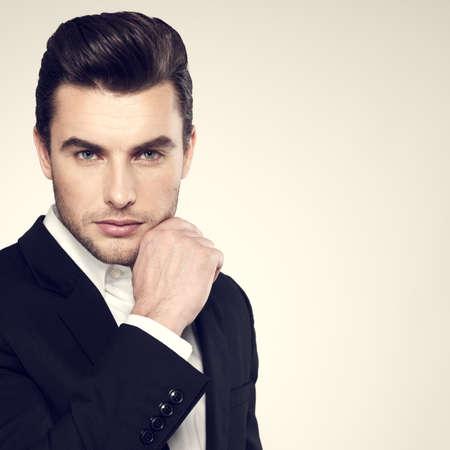 Mode junger Geschäftsmann schwarzen Anzug lässig posiert im Studio