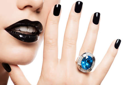 jewelry: Macro shot of a womans lips and nails painted bright color black. Person holds in mouth blue stone.