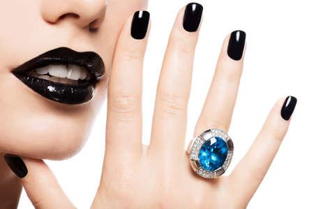 Makroaufnahme der Lippen und Nägel einer Frau gemalt helle Farbe schwarz. Person hält in den Mund, blauen Stein.