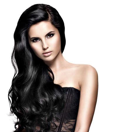 Mooie jonge brunette vrouw met lang zwart krullend haar poseren in studio
