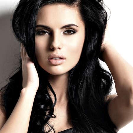 Hermosa sexy joven morena con el pelo largo. Retrato de un modelo de moda bonita que presenta en el estudio. Foto de archivo