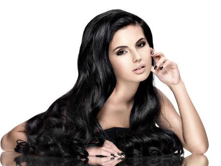 Bella giovane donna bruna con lunghi capelli neri ricci posa in studio Archivio Fotografico - 44650999