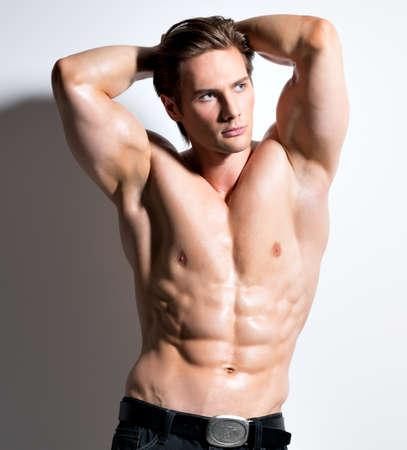 desnudo masculino: Retrato de un hombre guapo muscular atractivo con las manos detrás de la cabeza posando sobre un fondo blanco.