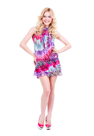 colorful dress: Full portrait of young smiling blonde woman in colorful dress posing at studio - isolated on white background. Stock Photo