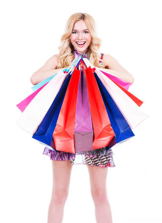 buyer: Happy young blonde woman with colored shopping bags in pink dress over white background. Stock Photo