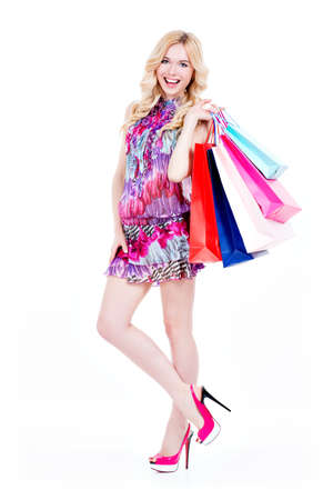 woman shop: Full portrait of happy young woman with purchasing in pink dress and high heels - isolated on a white background.