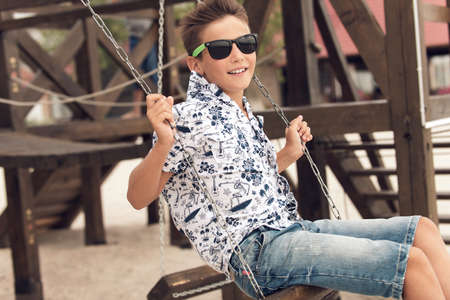 gafas de sol: Retrato de feliz adolescente sonriente en gafas de sol que se divierten en un columpio en un parque infantil de verano. Foto de archivo