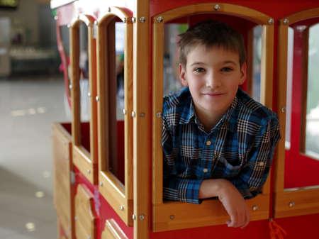 10s: Portrait of happy smiling teenage boy in the wood wagon train Stock Photo