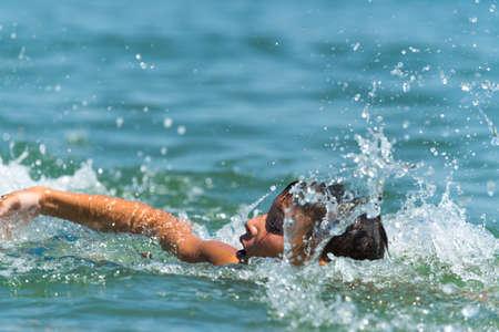 natacion: Diez años adolescente muchacho nada en el mar con grandes salpicaduras Foto de archivo