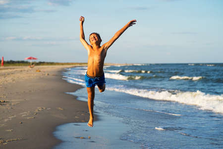 Happy boy jumps on the sea beach at summer. Kid with raised arms
