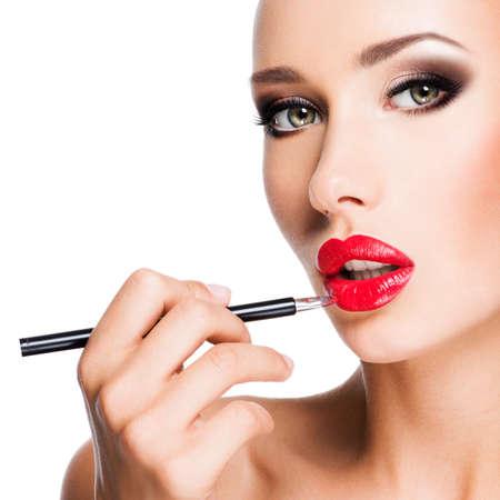 Frau, die roten Lippenstift mit Kosmetikstift auf den Lippen - isoliert auf weiß
