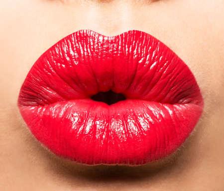 labios rojos: Los labios de la mujer con los labios pintados de rojo y el gesto beso