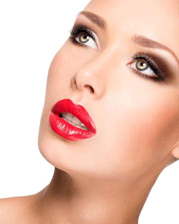 labios sexy: Primer retrato de una hermosa mujer de moda joven con el maquillaje glamour posando en el estudio aislado en blanco.