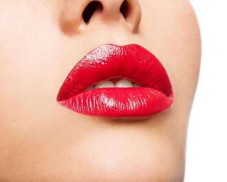 labios rojos: Los labios de la mujer con los labios pintados de rojo. La manera del encanto del lustre maquillaje brillante. Foto de archivo
