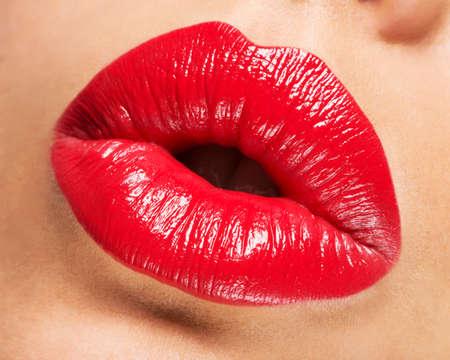 beso labios: Los labios de la mujer con los labios pintados de rojo y el gesto beso