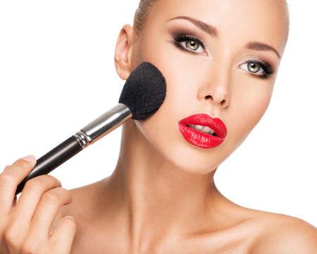 maquillage: Portrait Gros plan d'une femme appliquant Fondation tonale cosmétique sèche sur le visage à l'aide pinceau de maquillage.