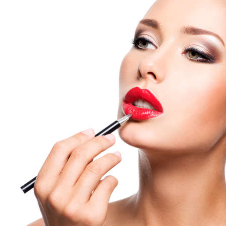 applying: Woman applying red lipstick with cosmetic pencil on the lips - isolated on white
