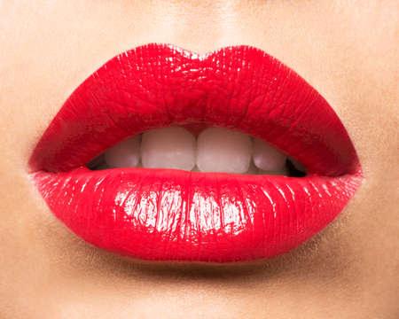 Los labios de la mujer con los labios pintados de rojo. La manera del encanto del lustre maquillaje brillante. Foto de archivo