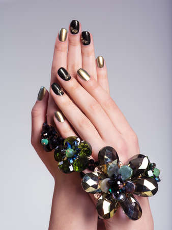 Beautiful womans nails with  creative manicure and jewelry. Studio image Stock Photo