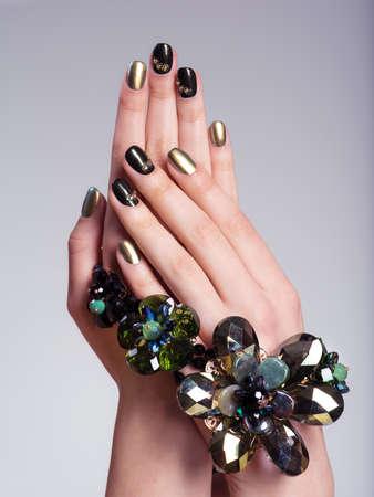 Mooie vrouw spijkers met creatieve manicure en sieraden. Image studio