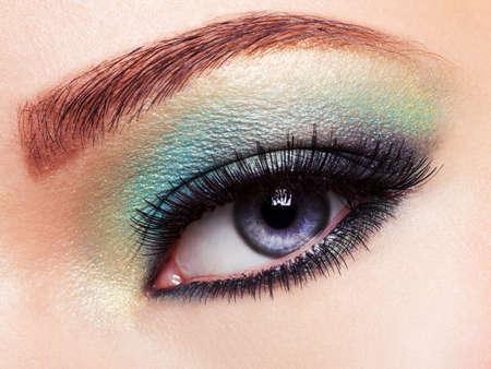 long: Womans eye with green eye make-up. Long eyelashes