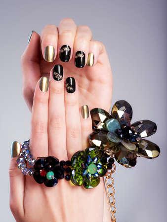 manicura: Uñas de la mujer hermosa con la manicura creativo y joyas. Imagen del estudio