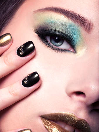 motton blue: Close-up woman face with green eye make-up. Stock Photo